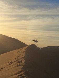 Young girl turning a cartwheel atop a sand dune against the twilight sky